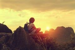 viajante que senta-se na montanha superior com vista do por do sol foto de stock royalty free