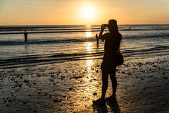 Viajante que toma uma foto do por do sol na praia de Kuta, Bali Imagem de Stock Royalty Free