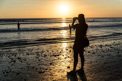 Viajante que toma uma foto do por do sol na praia de Kuta, Bali Imagens de Stock