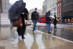 Viajantes de bilhete mensal ocupados de Londres na chuva de derramamento Fotografia de Stock