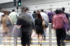 Viajantes de bilhete mensal que cruzam a rua ocupada de Hong Kong Fotografia de Stock Royalty Free
