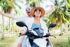 Viajantes de sorriso felizes dos pares que montam o 'trotinette' do velomotor sob palmeiras Imagem tropical do conceito das f?ria imagem de stock royalty free