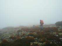 Viajantes dos turistas com trouxas que andam através das rochas na névoa grossa do leite Imagem de Stock Royalty Free
