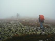 Viajantes dos turistas com trouxas que andam através das rochas na névoa grossa do leite Fotografia de Stock