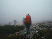 Viajantes dos turistas com trouxas que andam através das rochas na névoa grossa do leite Fotografia de Stock Royalty Free
