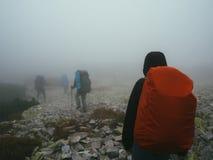 Viajantes dos turistas com trouxas que andam através das rochas na névoa grossa do leite Fotos de Stock
