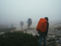 Viajantes dos turistas com trouxas que andam através das rochas na névoa grossa do leite Imagem de Stock