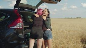 Viajantes fêmeas que discutem o material de embalagem no tronco de carro video estoque