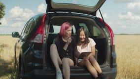 Viajantes fêmeas que usam o PC da tabuleta no tronco de carro vídeos de arquivo