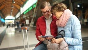 Viajantes, marido e esposa, bilhetes da verificação com uma programação, sentando-se em um banco na construção da estação de trem filme