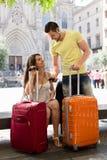 Viajantes novos agradáveis que usam o sistema de navegação do telefone Fotografia de Stock Royalty Free