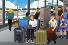 Viajantes que carregam seus dispositivos eletrónicos em um aeroporto Fotografia de Stock Royalty Free