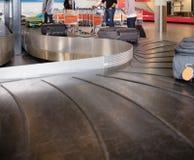 Viajantes que esperam a bagagem da correia transportadora no aeroporto Foto de Stock