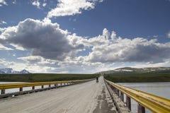 Viajar a la bici en el puente del río de Susitina Imagen de archivo libre de regalías