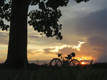 Viajar a la silueta de la bici en la puesta del sol Foto de archivo