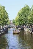 Viaje al barco con los turistas en un canal, Amsterdam, Países Bajos Foto de archivo libre de regalías