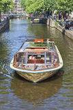 Viaje al barco con los turistas en un canal, Amsterdam, Países Bajos Imagen de archivo libre de regalías