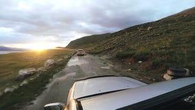 Viaje auto: SUV monta en un camino de la alta montaña después de lluvia en la puesta del sol sobre un río POV - Point of View de  metrajes