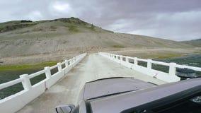Viaje auto: SUV monta en un camino de la alta montaña en el puente blanco sobre un río POV - Point of View de un coche que mueve  almacen de metraje de vídeo