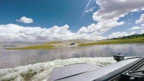 Viaje auto: SUV mueve el flujo del río Un coche grande monta en un camino de la alta montaña sobre un río peligroso de la montaña almacen de metraje de vídeo