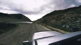 Viaje auto: un coche grande mueve adelante el campo SUV monta en un camino de la alta montaña sobre un río peligroso de la montañ metrajes