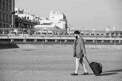 Viaje barbudo del inconformista del hombre con el bolso grande del equipaje en las ruedas Viaje dejado comenzar El viajero con la fotos de archivo libres de regalías