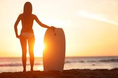 Viaje bodyboarding de la playa de la mujer de la persona que practica surf del deporte acuático Fotos de archivo libres de regalías