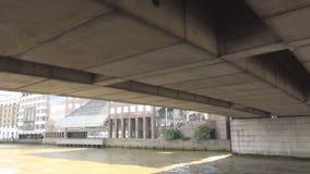Viaje con un barco turístico en el río Támesis debajo de un puente en Londres en el centro de la ciudad almacen de video