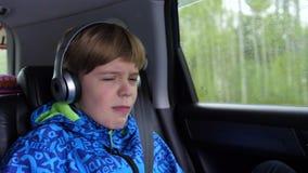 Viaje de la familia La familia está conduciendo en la carretera Sentada adolescente en el coche y el escuchar la música a través  almacen de video