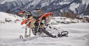 Viaje de la moto de nieve del snowbike de Enduro con la bici de la suciedad alta en las montañas Imagen de archivo libre de regalías