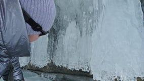 Viaje de la mujer en el hielo del lago Baikal Viaje a la isla del invierno La muchacha está caminando en el pie de rocas del hiel metrajes