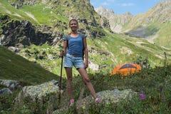 Viaje de la mujer joven con la mochila en montaña Imagen de archivo