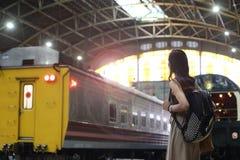 Viaje de la mujer solamente por el tren que busca la estación imagenes de archivo