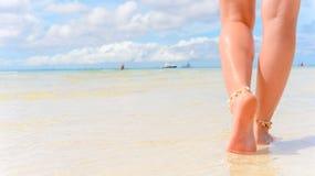 Viaje de la playa - mujer que camina en la playa de la arena Detalle del primer de pies femeninos y de la arena de oro imágenes de archivo libres de regalías