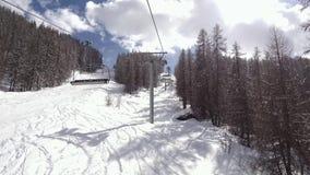 Viaje de las vacaciones de invierno en la telesilla sobre estación de esquí metrajes