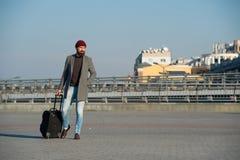 Viaje de negocios Viaje barbudo del inconformista del hombre con el bolso grande del equipaje en las ruedas Viaje dejado comenzar foto de archivo libre de regalías