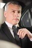Viaje de negocios. Hombre de negocios mayor confiado que se sienta en la parte posterior Foto de archivo libre de regalías