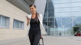 Viaje de negocios Mujer hermosa con el teléfono y la maleta metrajes