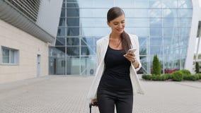 Viaje de negocios Mujer hermosa con el teléfono y la maleta almacen de metraje de vídeo