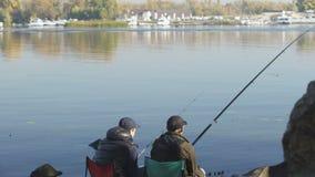 Viaje de pesca de los amigos, gente que se sienta en lugar hermoso y que admira la visión almacen de metraje de vídeo