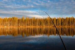 Viaje de pesca a Tuusjärvi El lago tranquilo, árboles se duplica de wa Imagenes de archivo