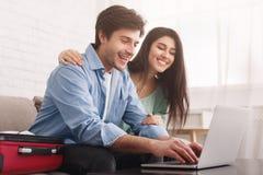 Viaje de planificación de los pares felices, boletos de reservación en línea en el ordenador portátil fotos de archivo