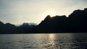Viaje del barco en el agua del lago del lago, de montañas, de acantilados y de rocas tropicales durante puesta del sol metrajes