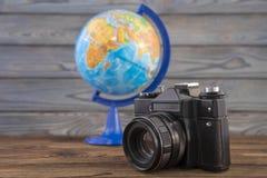 Viaje del concepto, globo y cámara del vintage en un fondo de madera Foto de archivo