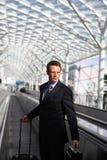 Viaje del hombre de negocios con el bolso y la carretilla en las escaleras móviles Foto de archivo