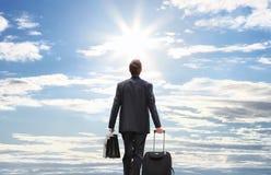 Viaje del hombre de negocios con la carretilla que camina al cielo Fotos de archivo