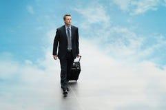 Viaje del hombre de negocios el fondo del cielo que se nubla concepto computacional Imagen de archivo