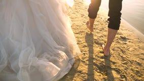 Viaje del hombre y de la muchacha en la playa Primer novia en un vestido blanco y el novio que camina descalzo en el agua en metrajes