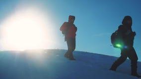 Viaje del invierno del negocio del trabajo en equipo turistas de los hombres que suben la silueta máxima de la luz del sol del eq almacen de video