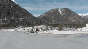 Viaje del invierno, vista aérea del complejo del resto para los turistas en el lago helado en montañas con los árboles contra el  almacen de video